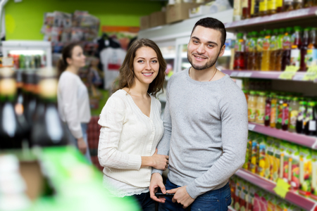 canned goods: Portrait young couple standing near shelves with canned goods at shop Stock Photo