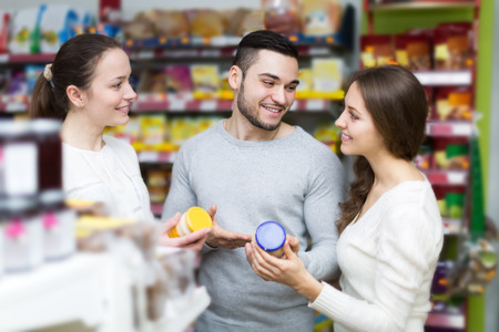canned goods: adult russian customers standing near shelves with canned goods at shop Stock Photo