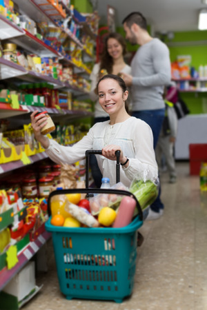 canned goods: Positive europen customers standing near shelves with canned goods at shop Stock Photo