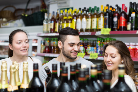 Adult people choosing alcoholic beverages in a liquor store