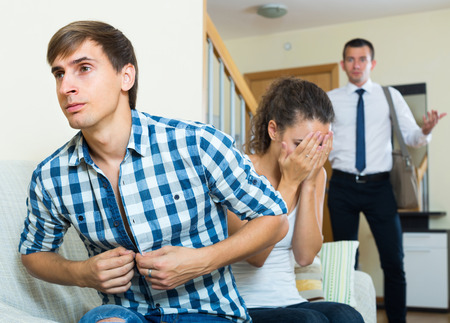 discovering: Shocked husband discovering young wife with lover on couch