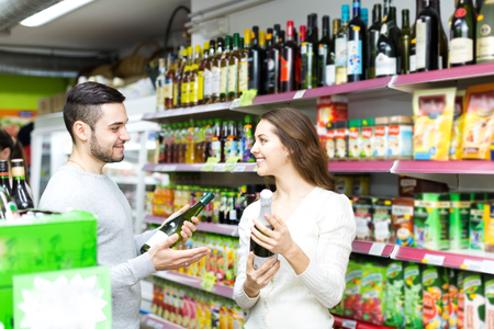happy customer: Two people in s supermarket alcohol section. Man gives woman an advice which wine to choose