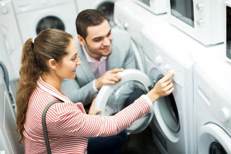 lavadora con ropa: Sonriente joven pareja familia comprar nueva lavadora de ropa en un supermercado. Centrarse en el hombre Foto de archivo