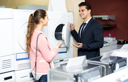 clothes washer: Happy family couple buying new clothes washer in supermarket. Focus on the man