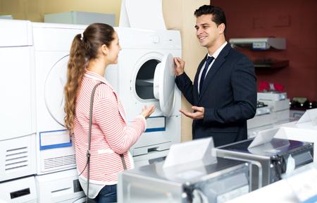 lavadora con ropa: Pareja feliz de la familia la compra de nueva lavadora de ropa en un supermercado. Centrarse en el hombre