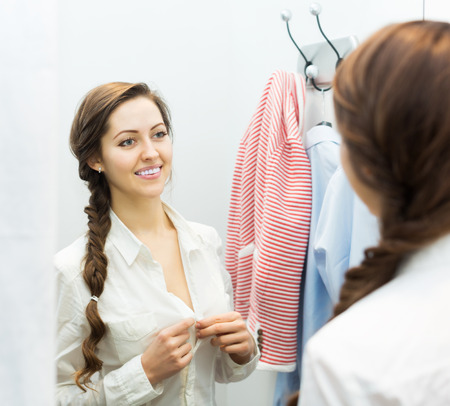 brune: Attractive positive girl trying on new blouse at apparel store