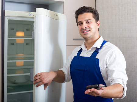 serviceman: Serviceman fixing technical problems with fridge in domestic  interior
