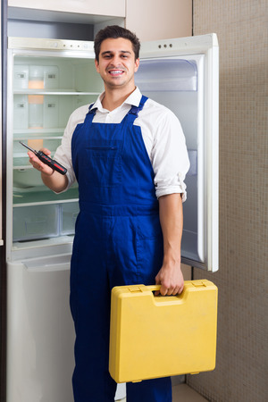 refrigerator kitchen: Smiling adult handyman repairing refrigerator in kitchen Stock Photo