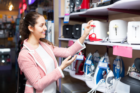 domestic appliances: Happy female customer looking at toasters in domestic appliances section