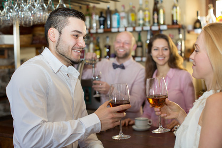 entertaining: Happy bartender entertaining guests at bar counter in bar