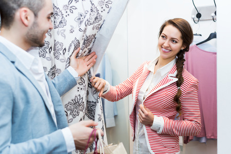 spouses: Positive young spouses standing at boutique changing cubicle Stock Photo