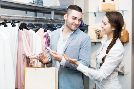 store clerk: Positive store clerk serving young purchaser at fashionable apparel store