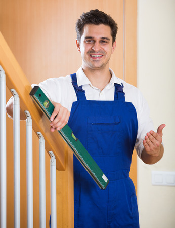 construction level: Positive handyman fixing stairway railing in new apartment Stock Photo