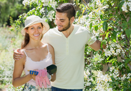 floriculturist: Young married couple planting plants in garden at summer day