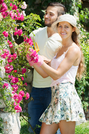 floriculturist: Young family with gardening tool working in their backyard garden