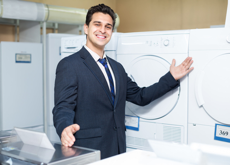 sales manager: Cheerful smiling sales manager showing goods at household appliances section Stock Photo