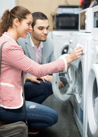 familias felices: clientes que sonríe mirando la máquina de lavandería en la sección de aparatos electrodomésticos
