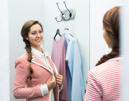 cubicle: Smiling attractive girl standing at boutique changing cubicle