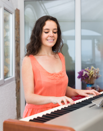 rehearse: Young smiling female musician playing sequencer indoor