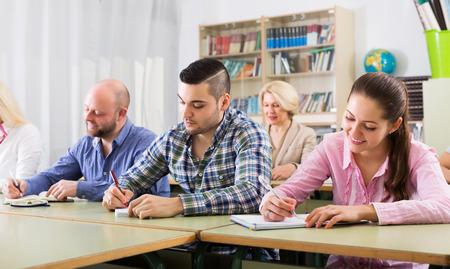 cuadro sinoptico: Estudiantes alegres de diferente edad en cursos de extensión en el aula Foto de archivo