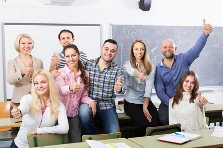 cohesive: Portrait of smiling teacher and adult students in classroom Stock Photo