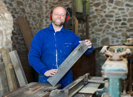 woodcutting: Smiling craftsman working on a woodcutting machine at guitar workshop Stock Photo