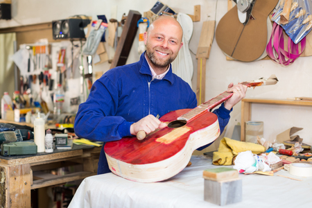 toolroom: Happy guitar-maker working with unfinished guitar at workshop