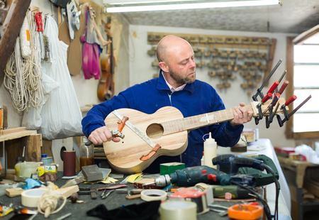 craftman: Craftman working with unfinished guitar at workshop