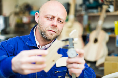 woodworker: Portrait of professional woodworker on lathe at musical instrument workroom
