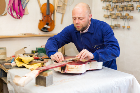toolroom: Portrait of serious craftsman holding unfinished guitar indoors Stock Photo