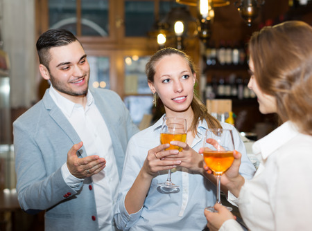 acquaintance: Casual acquaintance of smiling young adults at bar. Selective focus on girl