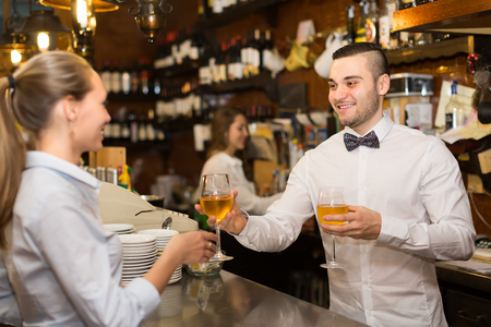 bartenders: Positive happy female drinking wine at counter and chatting with bartenders Stock Photo