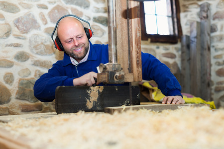 woodworker: Portrait of successful professional woodworker on lathe at musical instrument workroom