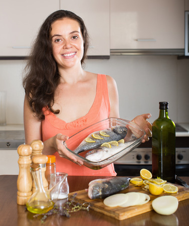 cook griddle: Happy  housewife cooking fish  in frying pan at home kitchen