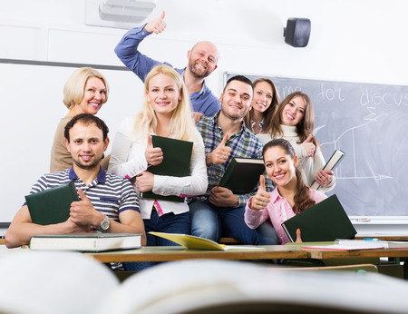 cohesive: Portrait of friendly smiling teacher and adult happy students in classroom