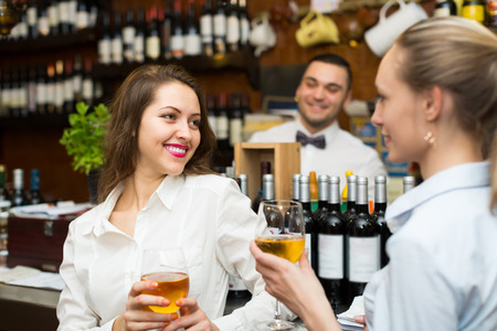 barmen: Young bartender and two smiling women with wine at bar