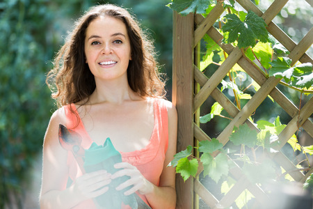 undercut: Smiling young woman working with pruning scissors in the garden