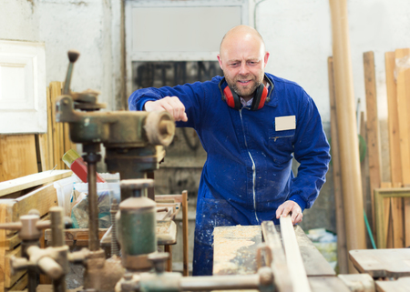 toolroom: concentrated male worker on lathe at  wood workroom Stock Photo