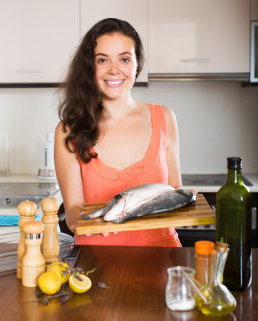 gilthead bream: Happy young woman holding raw fish at home kitchen
