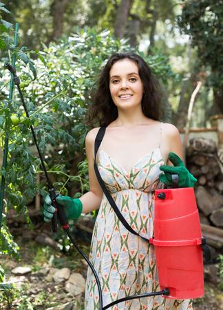 knapsack: Happy woman working in garden with knapsack garden spray Stock Photo