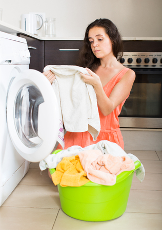 the weariness: Tired woman doing laundry with washing machine at home kitchen