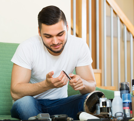 positiv: Positive young handsome brunet doing manicure at home Stock Photo