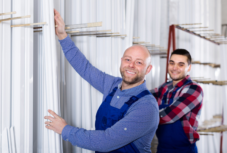 toolroom: Couple of males  inspecting window frames at factory