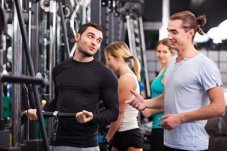 powerlifting: Young adults doing powerlifting on machines at fitness club Stock Photo