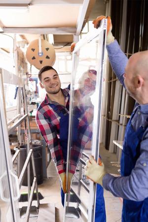 glasswear: Two  workers in uniform inspecting windows at workshop