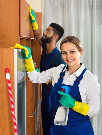 dusting: Professional smiling young cleaners cleaning and dusting in ordinary house