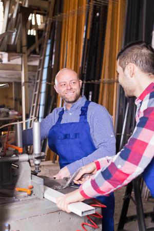toolroom: Two happy workmen in uniform working on machine in PVC shop Stock Photo