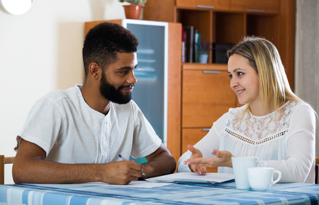 health insurance: Young adults preparing banking documents for health insurance at home