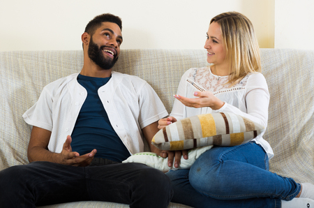 talking: Young interracial couple talking in domestic interior