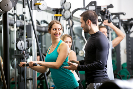 anaerobic: Smiling active people having weightlifting training in health club. Focus on the woman Stock Photo